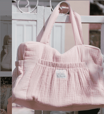 sac à langer Made in France en gaze de coton rose pale accroché à un portail en fer forgé blanc de la marque Blonde et Brune en Layette. Photo Instagram